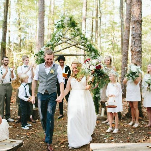 wedding couple walking down woodland ceremony isle with wedding party in the background