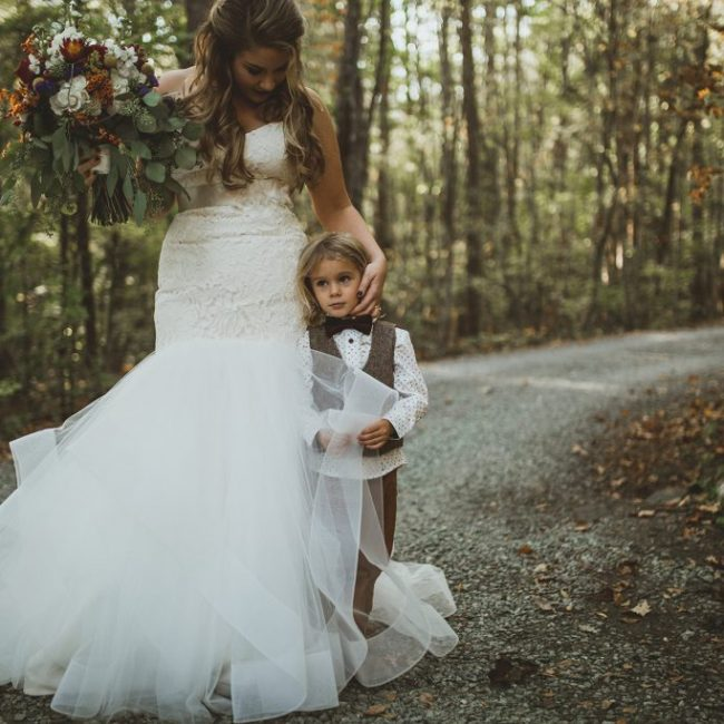 Wedding bride holding flowers with her son by her side outside in fall