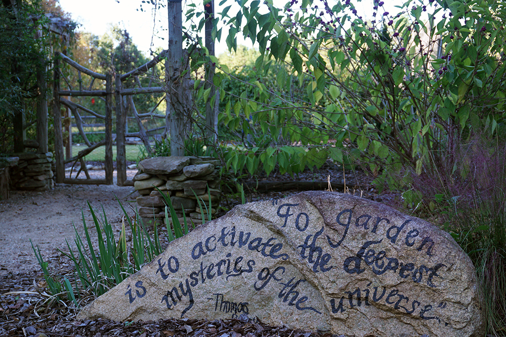 "detailed shot of large boulder with the words written ""To garden is to activate the deepest mysteries of the universe."" quote by Thomas Berry"