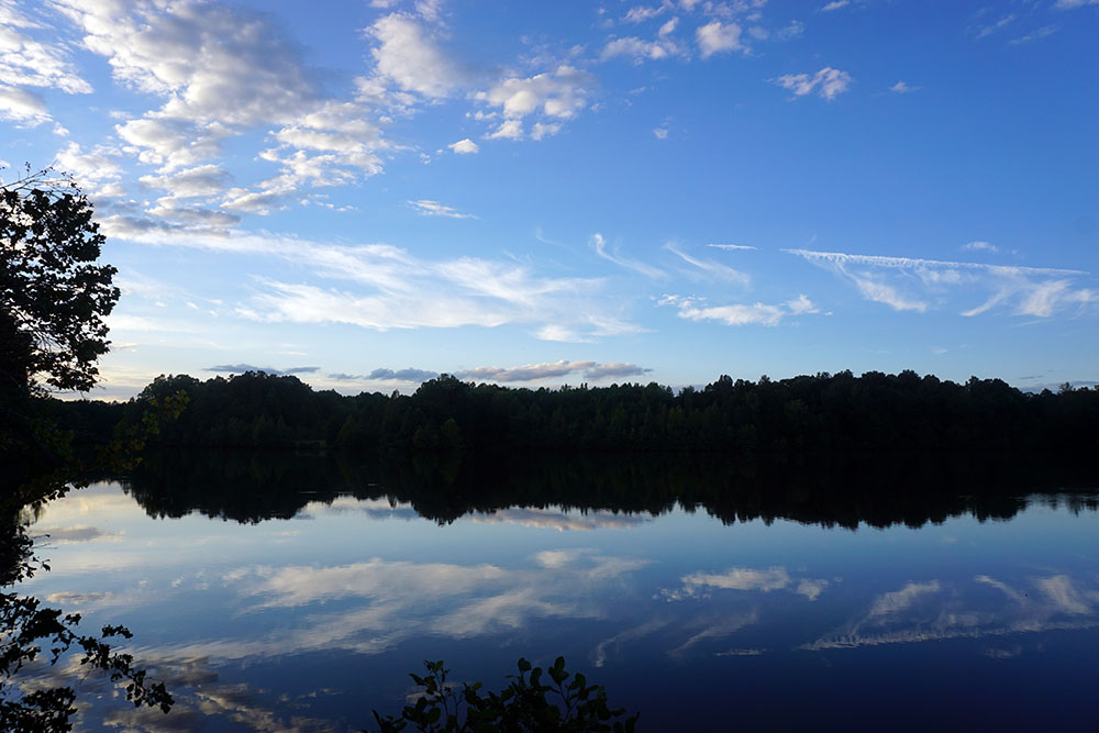 Beautiful lake scene featuring the reflection of bright blue sky and clouds