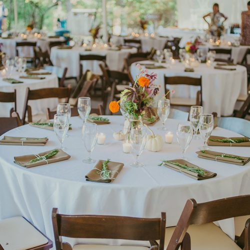 wedding reception dining setup featuring round tables with brown chairs and white linens