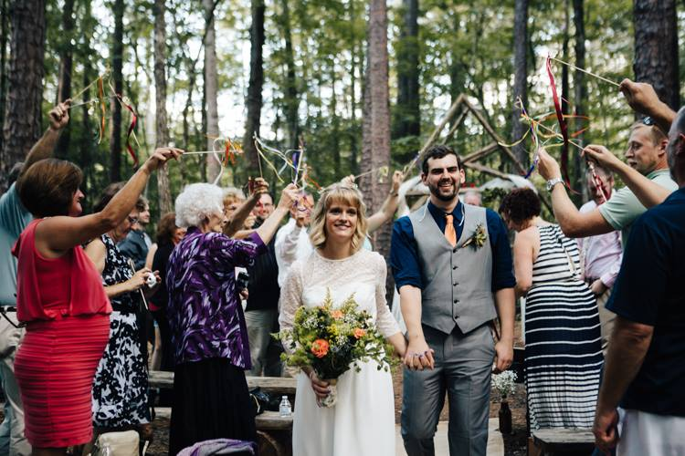 couple walking down the isle in the woodland ceremony site while guests celebrate with streamers