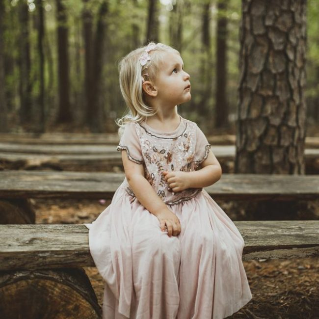 little girl in blush dress sitting on a bench in the woodlands looking up