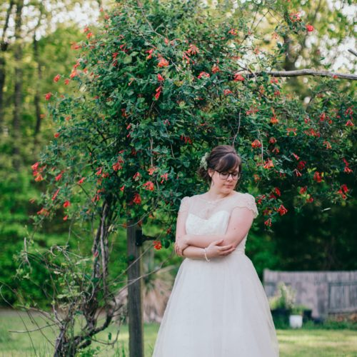 full length bridal portrait of woman wearing glasses looking down at shoulder beside a red honeysuckle b