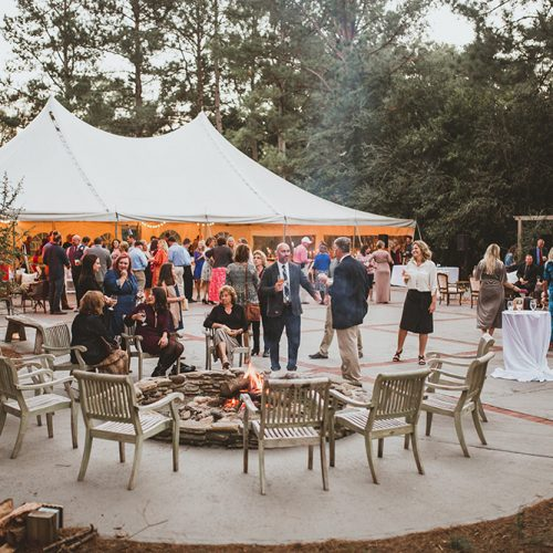 Outdoor wedding reception featuring white tent and courtyard with guests sitting by the fire and socializing