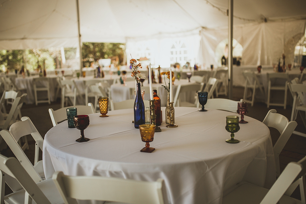 wedding reception dining setup under white tent with colorful dish ware and white linens