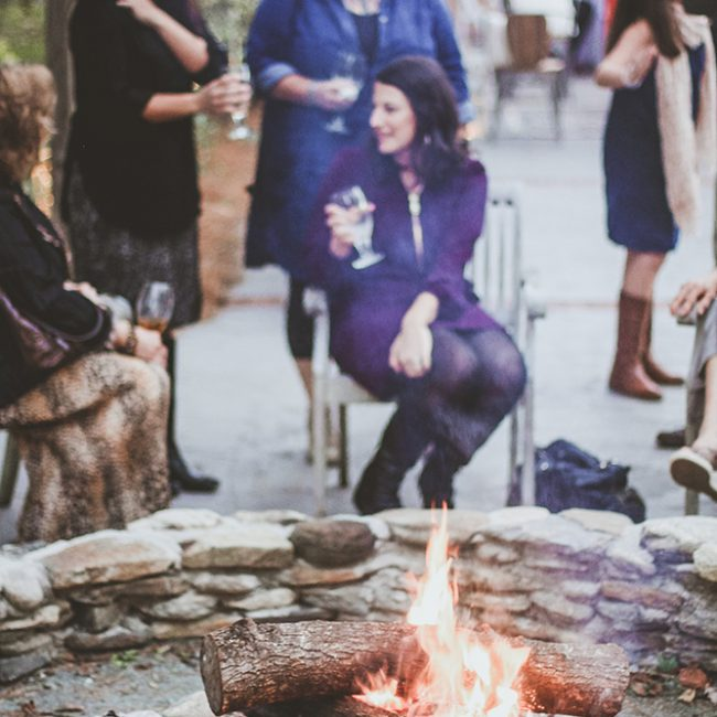 wedding reception detail shot of women drinking wine by the fire