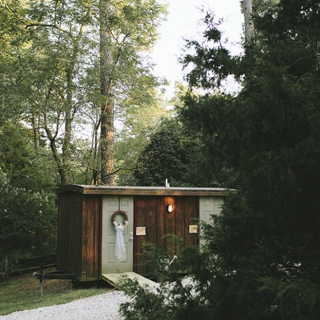 Outdoor wedding reception featuring restrooms tucked among trees