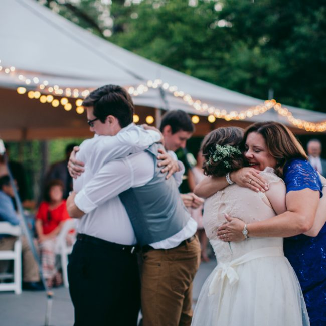 wedding couple hugging guests outside